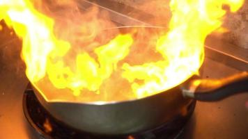 Slow motion - Chef cooking with flame in a frying pan on a kitchen stove.