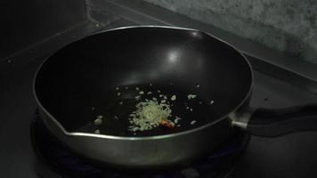 câmera lenta - chef cozinhando com chamas em uma frigideira no fogão.
