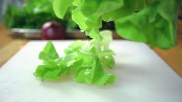 Zeitlupe - Nahaufnahme von Chefmann, der Salat gesundes Essen macht und Salat auf Schneidebrett in der Küche hackt.