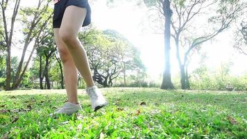 câmera lenta - saudável jovem asiática exercitando no parque. cabe jovem fazendo treino de treino de manhã. mulher asiática feliz alongamento no parque após a corrida de treino. exercício conceito ao ar livre.