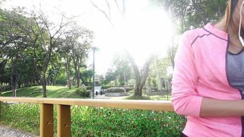 câmera lenta - uma linda mulher asiática em roupas de ginástica está usando um smartwatch para ouvir música, falando ao telefone depois de correr no parque. atraente corrida feminina saudável.