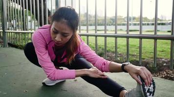 fitness esporte menina moda sportswear fazendo exercícios de ioga fitness na rua. cabe a jovem mulher asiática, fazendo exercícios de treinamento na manhã. jovem mulher asiática feliz alongamento no parque após a corrida de treino.
