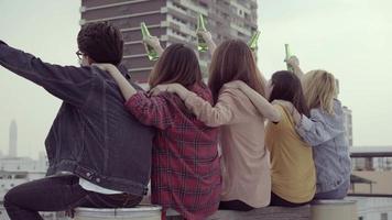 grupo de jovens mulheres asiáticas e pessoas do homem dançando e levantando os braços no ar ao som da música tocada por dj na festa urbana do sol no telhado. jovens asiáticas e amigos de rapaz a beberem video