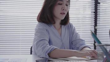 Beautiful young strain asian woman working on laptop while sitting in a living room at home. Asian business woman using phone for work in her home office. Enjoying time at home. video