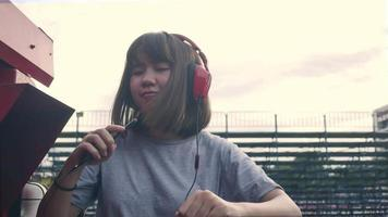 Beautiful young asian woman listening to music on a smart phone in the city. Young asian woman relaxing listening to music on the street. video