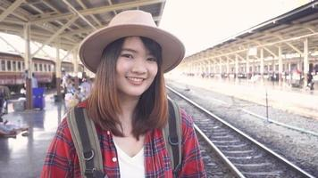 Slow motion - Happy Asian woman waiting the train at train station for travel in summer. Travel Thailand concept.