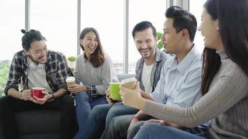diversità di giovani gruppo squadra in possesso di tazze di caffè e discutere di qualcosa con un sorriso mentre era seduto sul divano in ufficio. pausa caffè presso l'ufficio creativo.