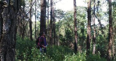 joven senderismo agua potable en la selva tropical con mochila.