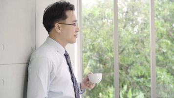 câmera lenta - empresário asiático maduro, bebendo um café e olhando pela janela para o horizonte da cidade de um prédio de escritórios.