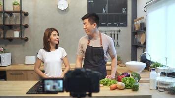 joven pareja asiática hombre y mujer en la cocina grabando video en la cámara.