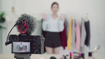 Blogger de moda asiática influyente en línea con bolsas de la compra y mucha ropa en el perchero para grabar un nuevo video de moda transmitido en vivo a una red social por Internet en casa.
