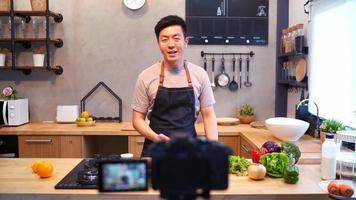 joven asiático en la cocina de grabación de vídeo en la cámara. sonriente hombre asiático trabajando en concepto de blogger de alimentos con frutas y verduras en la cocina.
