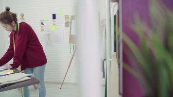 designer de moda jovem mulher asiática desenhando usando lápis e olhando para o papel enquanto trabalhava no estúdio da oficina. video
