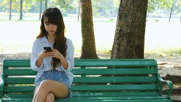 Linda jovem hippie triste mulher asiática emocionalmente ouvindo música em fones de ouvido com smartphone