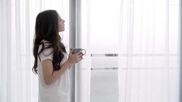 jovem mulher asiática apreciando seu café ou chá perto da janela molhada em seu quarto em casa. video