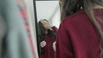 Ritratto di bella donna asiatica attraente che pettina i capelli e sceglie i vestiti nel suo camerino a casa.