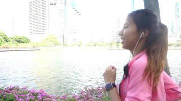 Slow motion - Young asian woman running on sidewalk in morning. video