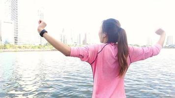 câmera lenta - mulher asiática bonita em roupas de ginástica está usando um smartwatch para ouvir música, falando ao telefone depois de correr no parque.