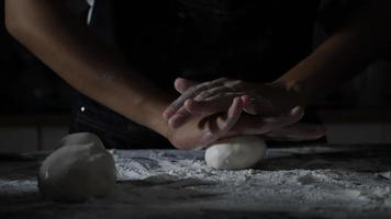 Slow motion of a women hand kneading flour and dough
