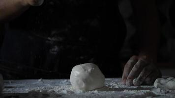 Slow motion of a woman's hands sifting flour over pizza dough