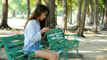 Cute woman is reading pleasant text message on mobile phone while sitting in the park in warm spring day