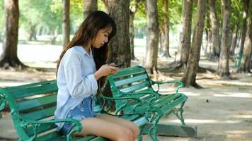 Mulher bonita está lendo mensagem de texto agradável no celular enquanto está sentada no parque em um dia quente de primavera