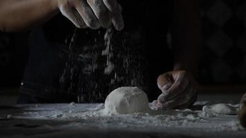 Slow motion of a woman's hands sifting flour over pizza dough video