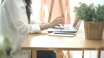 Beautiful young smiling Asian woman working on laptop while at home in office work space. video