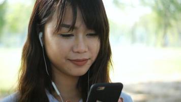 Mulher bonita está lendo mensagem de texto agradável no celular enquanto está sentada no parque em um dia quente de primavera video