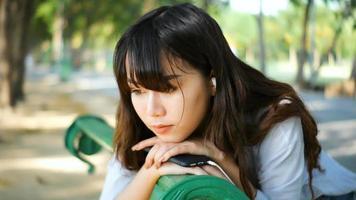 bela jovem hippie triste mulher asiática emocionalmente ouvindo música em fones de ouvido. video