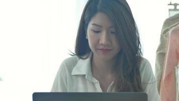 hermosa joven sonriente que trabaja en la computadora portátil mientras disfruta de beber café caliente sentado en una sala de estar en casa.