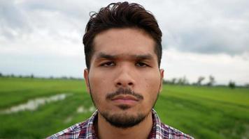 close-up de um homem com uma expressão séria enquanto ele está sozinho no campo