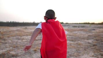 silueta de un niño divirtiéndose vestido como un superhéroe corriendo en un campo