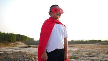 silhueta de um menino se divertindo vestido como um super-herói correndo em um campo video