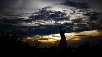 silhueta de uma menina feliz caminhando com o sol poente ao fundo video