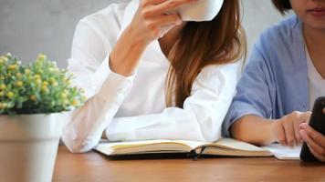 Las mujeres de negocios usan el teléfono móvil y escriben un informe sobre la mesa de madera.