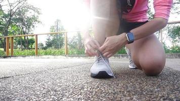 cámara lenta - cerca de mujer joven con cordones su zapato listo para entrenar en el ejercicio en el parque con luz cálida del sol en la mañana.