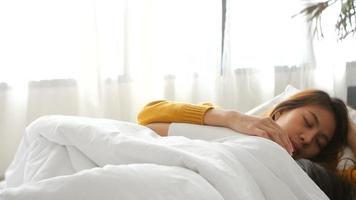 câmera lenta - belas jovens mulheres asiáticas abraçando e sorrindo enquanto deitavam juntos na cama, debaixo do cobertor em casa. video