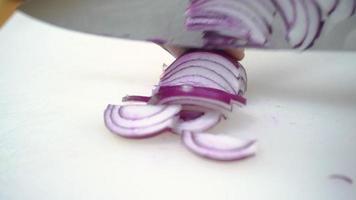 Zeitlupe - Nahaufnahme des Hauptmannes, der Salat gesundes Essen macht und Zwiebel auf Schneidebrett in der Küche hackt.