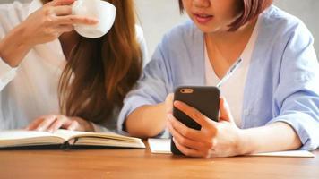Las empresarias utilizan el teléfono móvil y escriben un informe sobre la mesa de madera.