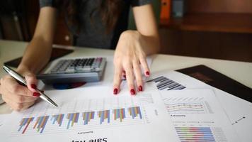 uma mulher usando as mãos como contabilidade em um escritório usando um laptop e uma calculadora video