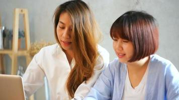 Two young business women sitting at table in cafe.
