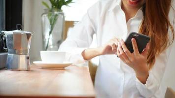 empresária usar telefone celular e beber café na mesa de madeira.