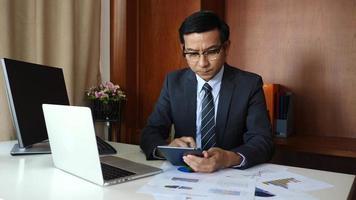 um empresário analisa planos de negócios para um projeto em um escritório. video