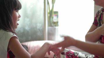 madre asiática está jugando con su hija en la sala de estar.