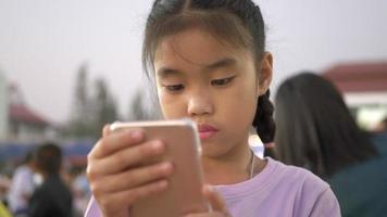 as meninas das crianças asiáticas na festa ao ar livre à noite e usam o smartphone.