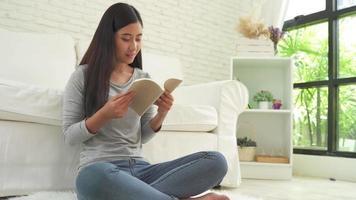 bella donna asiatica che gode del tempo e si siede sul divano moderno davanti alla finestra che si rilassa nel suo libro di lettura del soggiorno.