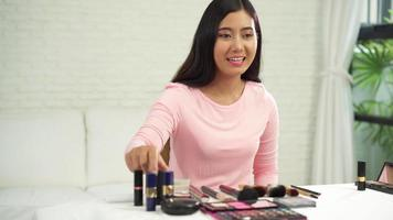 blogger de belleza presenta cosméticos de belleza mientras está sentado frente a la cámara para grabar videos. video