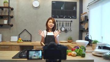 joven asiática en la cocina de grabación de vídeo en la cámara.