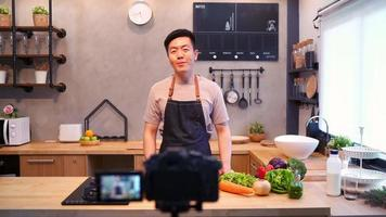 Young asian man in kitchen recording video on camera.